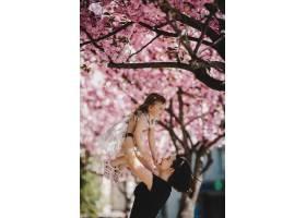 年轻漂亮的妈妈抱着可爱的小女儿站在盛开的_2914125