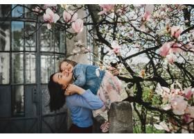 年轻漂亮的妈妈抱着可爱的小女儿站在盛开的_2914131