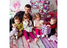 带着孩子坐在圣诞树附近的父亲_1617215
