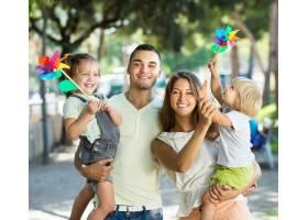 带着孩子玩风车的年轻父母_1631527