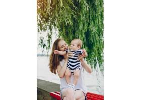 妈妈和儿子在公园里放松绕着河边散步_3191702