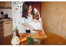 妈妈和女儿在家里的厨房里做蔬菜_2529097