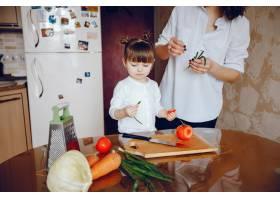 妈妈和女儿在家里的厨房里做蔬菜_2529100