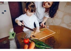 妈妈和女儿在家里的厨房里做蔬菜_2529107