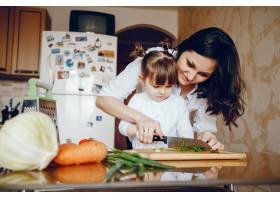 妈妈和女儿在家里的厨房里做蔬菜_2529108