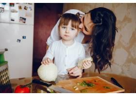 妈妈和女儿在家里的厨房里做蔬菜_2529110