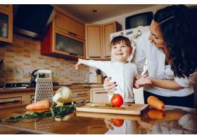 妈妈和女儿在家里的厨房里做蔬菜_2529113
