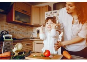 妈妈和女儿在家里的厨房里做蔬菜_2529115