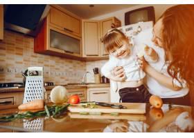 妈妈和女儿在家里的厨房里做蔬菜_2529117