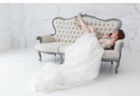 娇嫩的新娘躺在经典的沙发上讲手机_2462225