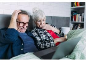 尴尬的老年夫妇在床上拿着笔记本电脑_2284873