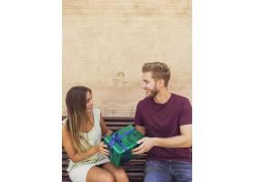 坐在长椅上拿着礼物的幸福夫妇_2982650