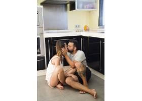 夫妻坐在厨房的地板上互相亲吻_3039183