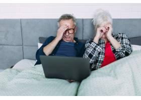 头疼的老年夫妇在床上用笔记本电脑_2284872