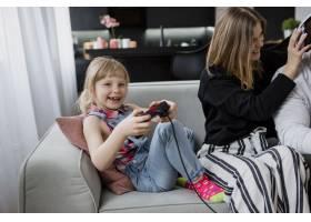 女孩在父母身边玩电子游戏_2221654