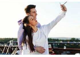 女孩和他的男朋友站在屋顶上自拍_2612657