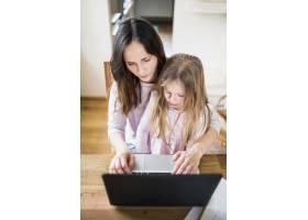 妇女和女儿在木桌上使用笔记本电脑的俯瞰视_2610743