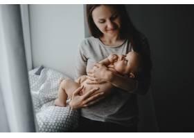 可爱的妈妈抱着快乐的新生儿站在明亮的窗户_2913996