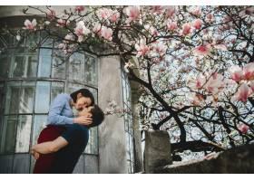 可爱的年轻夫妇站在外面盛开的树下温柔地_2914134