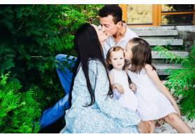 可爱的父母和他们坐在外面的小女儿温馨的亲_1617260