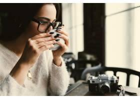 在明亮的咖啡馆里戴眼镜的女人在桌子旁喝_1621042