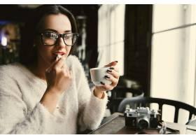 在明亮的咖啡馆里戴眼镜的女人在桌子旁喝_1621046