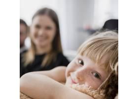 在父母身边拿着毛绒玩具的女孩_2177689