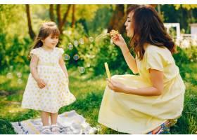 在绿树旁的一个夏季公园里妈妈穿着一件黄_2611968