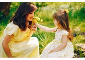 在绿树旁的一个夏季公园里妈妈穿着一件黄_2611973