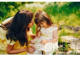 在绿树旁的一个夏季公园里妈妈穿着一件黄_2611974