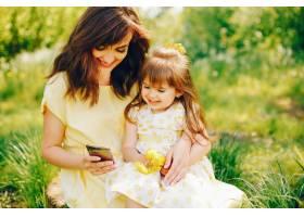 在绿树旁的一个夏季公园里妈妈穿着一件黄_2611977