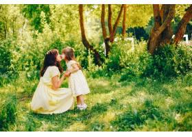 在绿树旁的一个夏季公园里妈妈穿着一件黄_2611979
