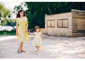 在阳光明媚的沙滩上妈妈穿着一件黄色连衣_2611984