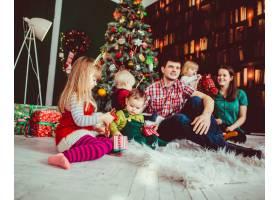 坐在圣诞树旁的父母和孩子们_1617118