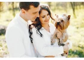 光明快乐的孕妇带着丈夫和狗走在公园里_2630579
