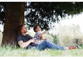 兴高采烈的父子俩在公园的树下玩耍玩得很_2438043
