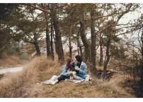 一对温文尔雅的情侣坐在秋天的公园里喝茶_2630630