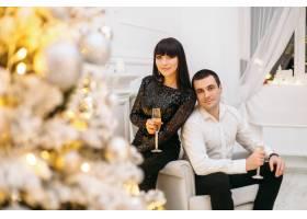 一对男男女女在一棵闪闪发光的圣诞树前穿着_2437624