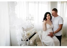 一对英俊的丈夫和漂亮的贪婪的女人在摄影棚_2877607
