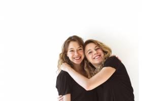 两个微笑的姐妹在白色背景上拥抱_3006337