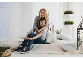 两个成年姐妹温柔地拥抱坐在白色的床上_2915374