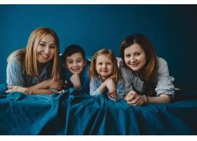 两位母亲和她们的孩子躺在蓝色的床上_2915375