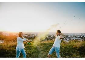 一男一女站在绿色的草坪上玩五颜六色的烟_2913976