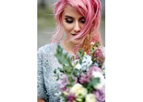 令人惊叹的粉色头发女人站在那里手持大束_1621125