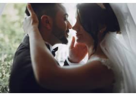 一个穿着黑色西装的漂亮年轻人和他的新娘站_2528646