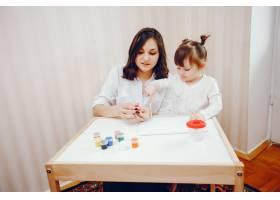 一位年轻的母亲和她的小女儿在纸上作画_2529142
