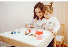 一位年轻的母亲和她的小女儿在纸上作画_2529144