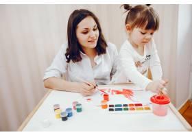 一位年轻的母亲和她的小女儿在纸上作画_2529145