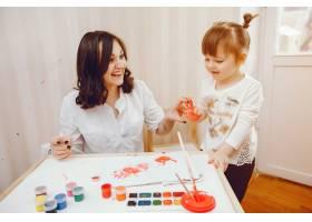 一位年轻的母亲和她的小女儿在纸上作画_2529149