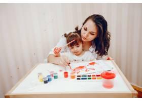一位年轻的母亲和她的小女儿在纸上作画_2529150
